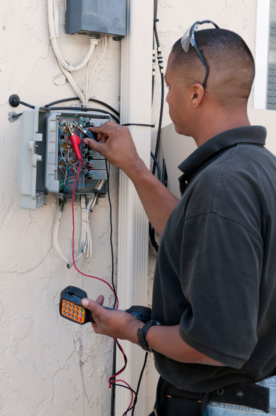 photo of technician testing electrical circuits in a home